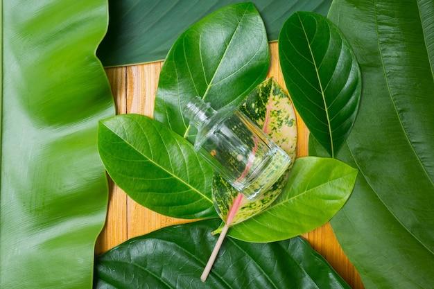 Récipients de bouteille cosmétiques naturels sur fond de feuille verte Photo Premium