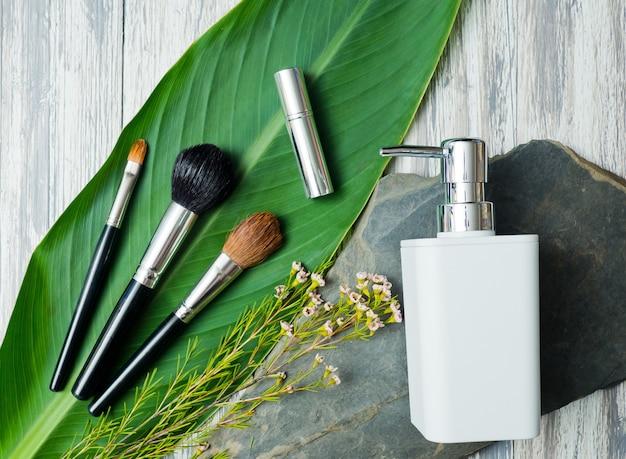 Récipients de bouteille de cosmétiques naturels sur fond de feuille verte Photo Premium