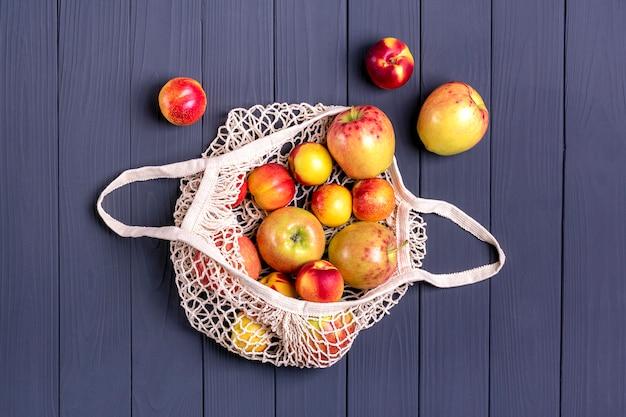 Récolte d'automne. sac de magasinage en filet écologique avec pomme juteuse et nectarine sur une surface en bois gris foncé. Photo Premium