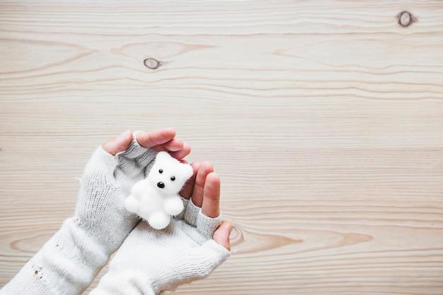 Récolte des mains dans les mitaines tenant l'ours blanc Photo gratuit