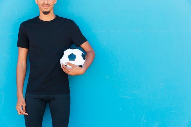 Récolte De Sportif Ethnique Avec Ballon De Foot Sous Le Bras Photo gratuit