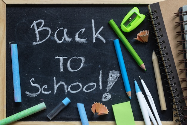 Rédaction à main levée retour aux lettres d'école sur tableau noir avec des fournitures scolaires Photo Premium