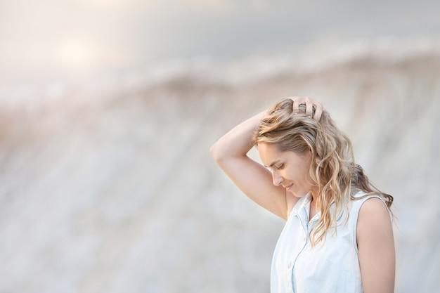 Réfléchi Jeune Femme Debout Contre Les Collines De Sable Clair. Photo Premium