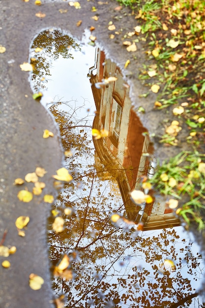 Reflet dans une flaque d'une vieille maison en automne Photo Premium