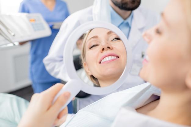 Reflet Dans Le Miroir D'un Sourire Sain De Jolie Jeune Patiente Souriante Des Cliniques Dentaires Après La Procédure De Blanchiment Des Dents Par Son Dentiste Photo Premium