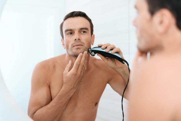 Le reflet miroir de l'homme se brosse les dents dans la salle de bain. Photo Premium