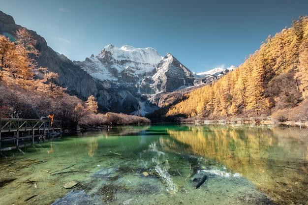 Reflet de la montagne xiannairi sur le lac émeraude avec forêt de pins dorés en automne Photo Premium