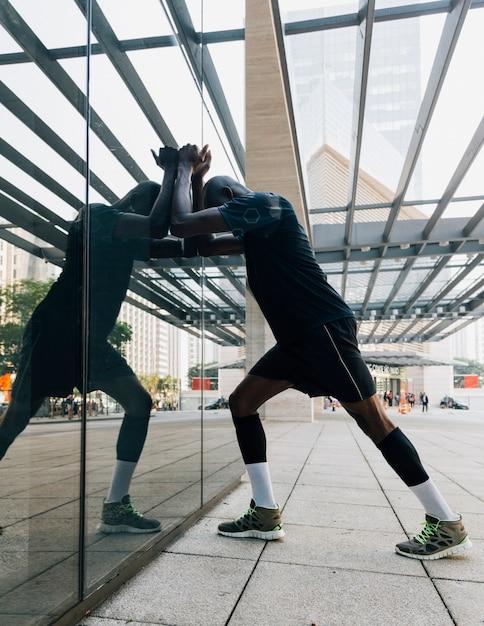 Réflexion d'athlète masculin qui s'étend de son muscle en s'appuyant sur le verre réfléchissant Photo gratuit