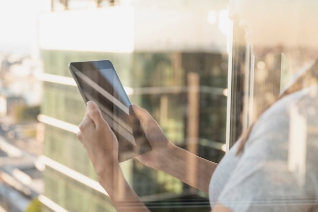 Réflexion sur la fenêtre d'une personne à l'aide d'une tablette Photo gratuit