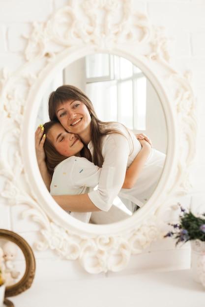 Réflexion de mère souriante embrassant sa fille Photo gratuit