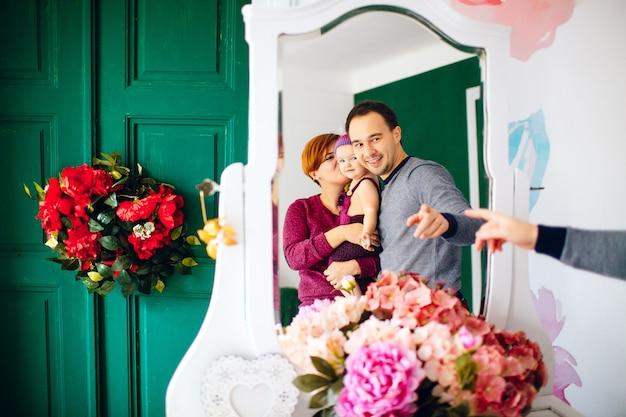 Réflexion de parents heureux avec petite fille en miroir blanc Photo gratuit