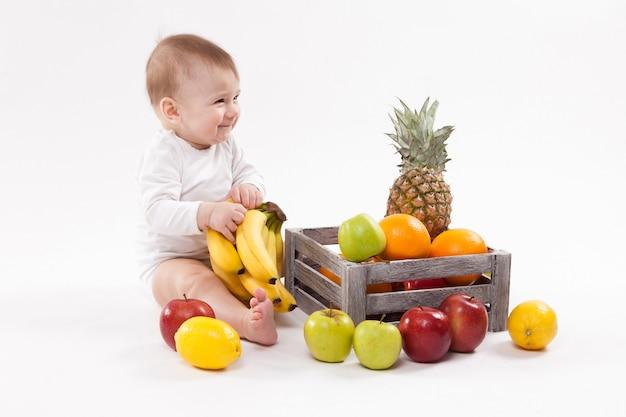 En Regardant Les Fruits Joli Bébé Souriant Sur Blanc Entre Fru Photo Premium