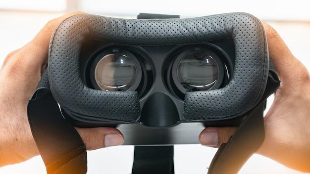 Regardant à l'intérieur d'un casque vr ou ar sur blanc. main tenant des lunettes vr. Photo Premium
