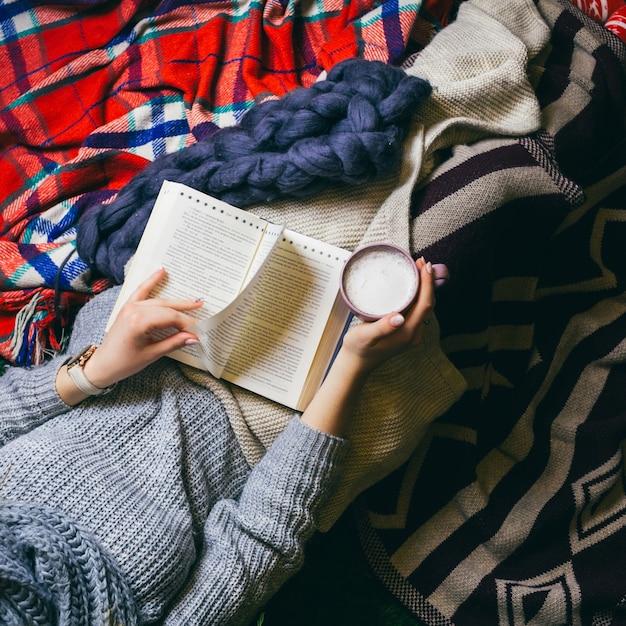 Regarde d'en haut chez une jeune femme qui prend du café alors qu'elle lit un livre Photo gratuit