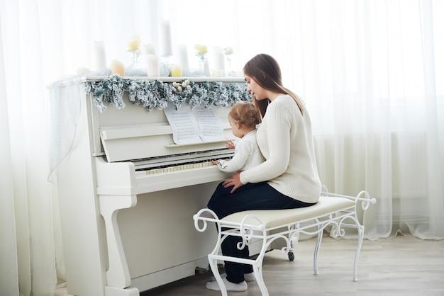Regarder par derrière la mère et la fille jouant du piano blanc Photo Premium