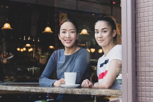 Regarder par la fenêtre de maman et sa fille assise dans un café avec une tasse de café. Photo Premium