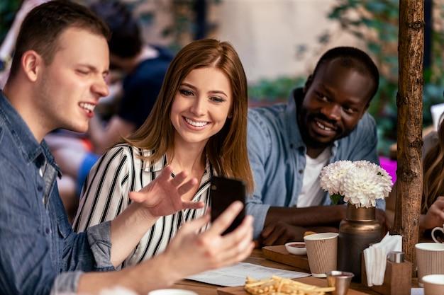 Regarder Une Photo Hilarante Sur Le Smartphone Lors De La Réunion Informelle Et Décontractée Avec Des Amis Proches Photo gratuit