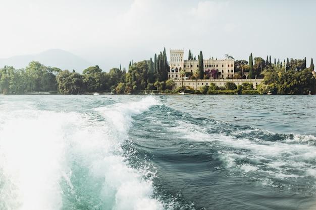 Regardez d'un bateau à la belle propriété sur le rivage. italie Photo gratuit