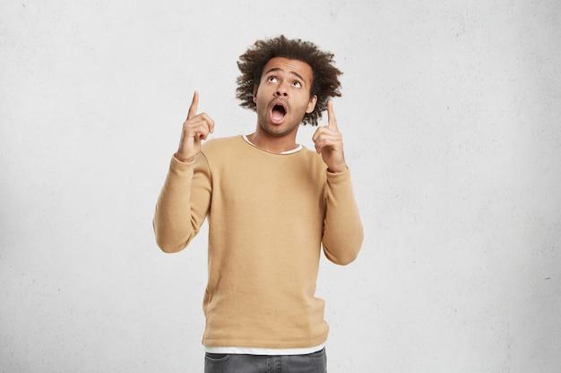 Regardez Là. Jeune Homme Stupéfait Avec Des Poils De Chaume Et Des Cheveux Touffus, Indique Par L'index Vers Le Haut Photo gratuit