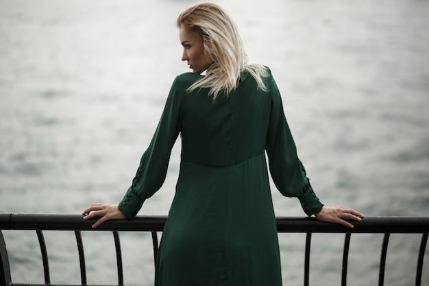 Regardez par derrière à la femme rêveuse en robe verte debout devant la rivière à new york Photo gratuit