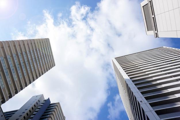 Regardez la vue et la récolte d'immeuble de bureaux sur fond de ciel bleu clair. avec un espace pour les textes Photo Premium