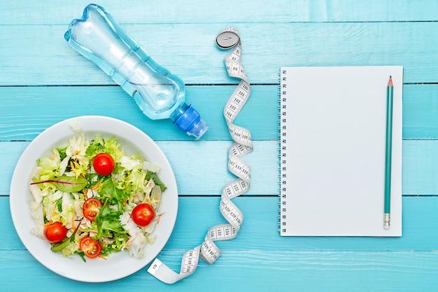 Régime alimentaire, menu ou programme, ruban à mesurer, eau et aliments diététiques Photo Premium