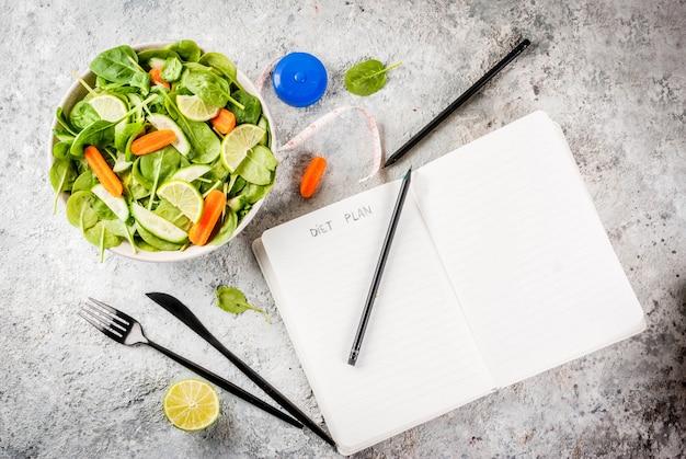 Régime alimentaire perdre du poids concept salade de légumes frais avec un couteau à fourchette note padgrey stone table Photo Premium