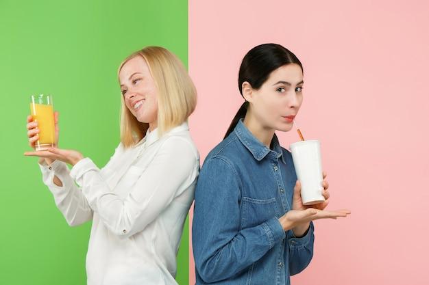 Régime. Concept De Régime. La Nourriture Saine. Belles Jeunes Femmes Choisissant Entre Le Jus D'orange Aux Fruits Et Une Boisson Sucrée Gazeuse Sans Hâte Photo gratuit