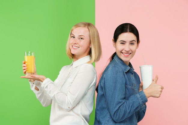 Régime. Concept De Régime. Nourriture Saine. Belles Jeunes Femmes Choisissant Entre Le Jus D'orange Et La Boisson Sucrée Gazéifiée Sans Honte Photo gratuit