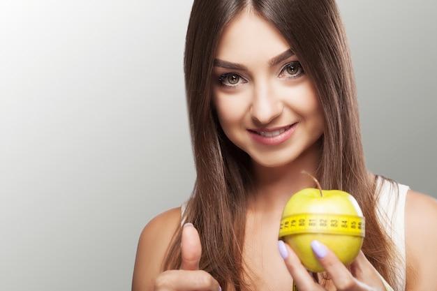 Régime. fitness une jeune fille adhère à un régime et tient une pomme avec un ruban à mesurer. perdre du poids. Photo Premium