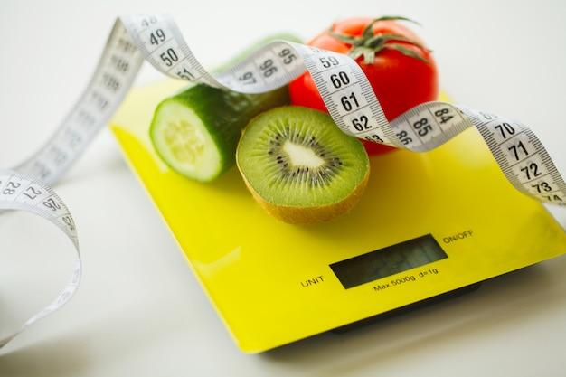 Régime. Fruits Et Légumes Avec Ruban à Mesurer Sur Une Balance Photo Premium