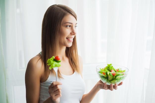 Régime. jeune femme mangeant de la salade et tenant une salade mixte Photo Premium