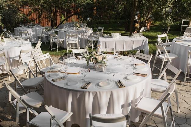 Réglage de la table de mariage. table de banquet pour les invités à l'extérieur avec vue sur la nature verdoyante Photo Premium