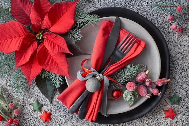 Réglage De La Table De Noël Sur Granit Gris, Assiettes, Vaisselle, Serviette Rouge Décorée De Baies Et De Poinsettia Photo Premium