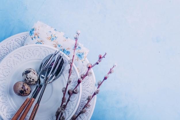 Réglage de la table de pâques. assiettes blanches, couverts, oeufs de caille et saule sur table bleue Photo Premium