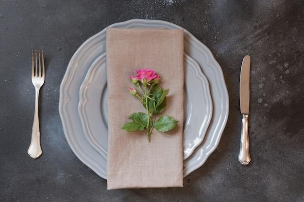 Réglage de la table romantique avec des roses roses comme décor, vaisselle vintage, argenterie. Photo Premium