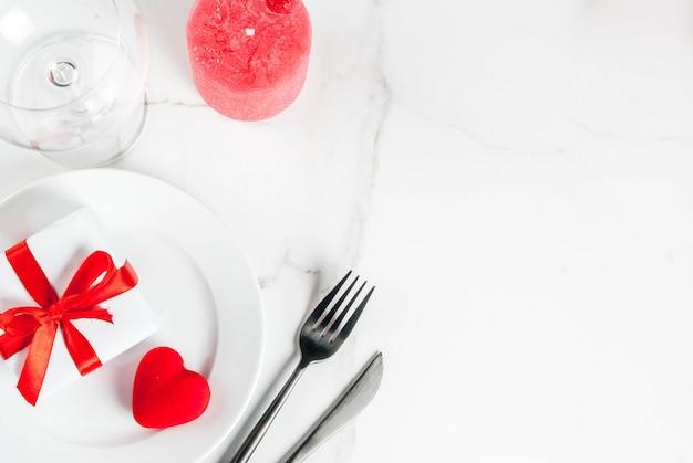 Réglage De La Table De La Saint-valentin Avec Assiette, Boîte-cadeau Et Coeur Rouge, Sur La Vue De Dessus De La Scène En Marbre Blanc Photo Premium