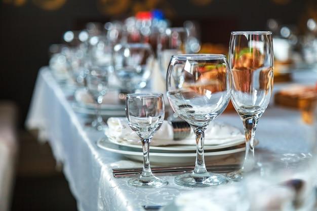 Réglage de la table avec des verres, des assiettes, des serviettes et de la nourriture Photo Premium