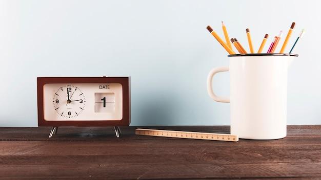 Règle et crayons près de l'horloge Photo gratuit