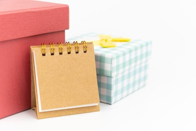 Remarque Papier Ou Calendrier Avec Deux Coffret Cadeau Sur Fond Blanc. Concept De Cadeau. Photo Premium