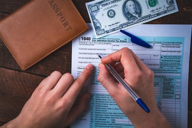 Remplir le formulaire d'impôt américain. formulaire d'impôt 1040, passeport, argent sur une table en bois. concept financier, concept fiscal déclaration de revenus individuelle. temps de paiement des taxes Photo Premium