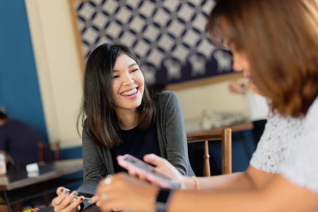 Rencontre freelance entre filles asiatiques avec une collègue au coffeeshop. Photo Premium