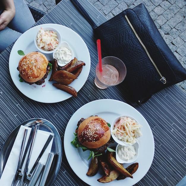 Rencontrer correctement une femme avec des hamburgers juteux et des pommes de terre au four Photo gratuit