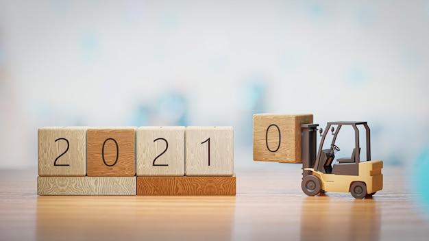 Rendu 3d. Chariot élévateur à Fourche Jusqu'à L'année 2021 Bloc De Bois Sur Le Mur Du Nouvel An Et De Noël. Photo Premium