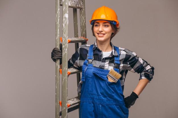Réparateur de femme avec échelle en uniforme isolé Photo gratuit