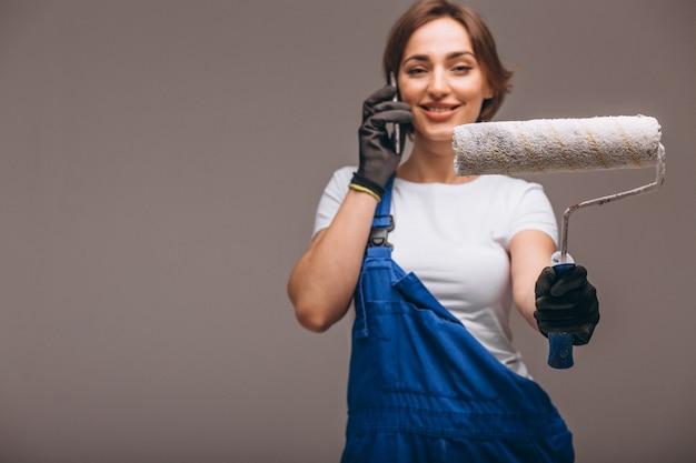 Réparateur de femme avec rouleau de peinture isolé parlant au téléphone Photo gratuit