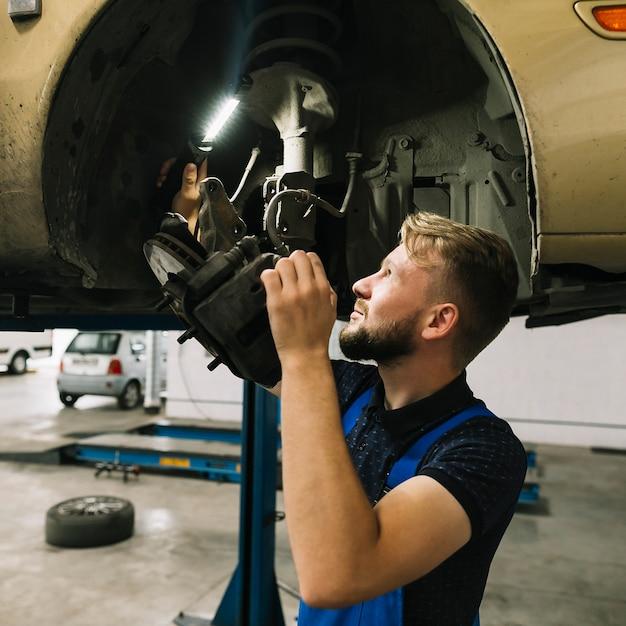 Réparateurs examinant la structure de la roue Photo gratuit