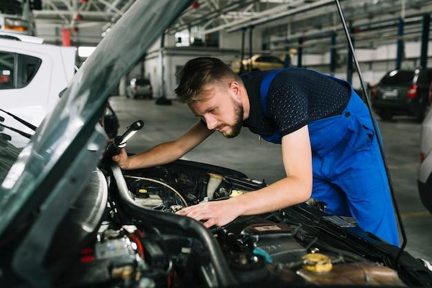 Réparateurs inspectant le moteur de la voiture Photo gratuit