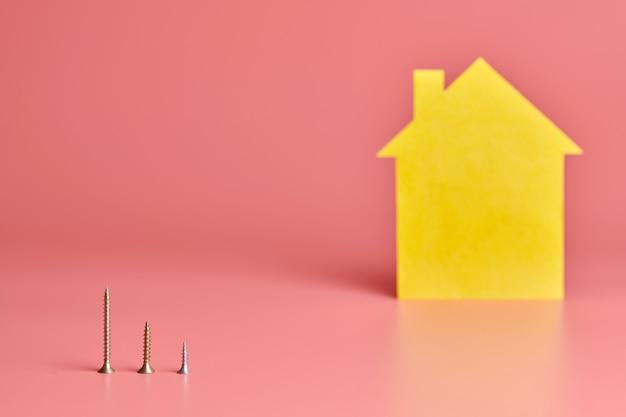 Réparation à Domicile Et Concept Redécoré. Rénovation De Maison. Vis Et Figure En Forme De Maison Jaune Sur Fond Rose. Photo Premium