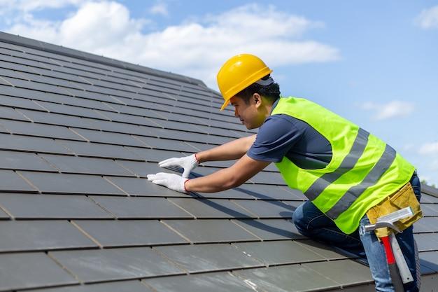 Réparation du toit, travailleur avec des gants blancs remplaçant les carreaux gris ou les bardeaux sur la maison avec du bleu Photo Premium